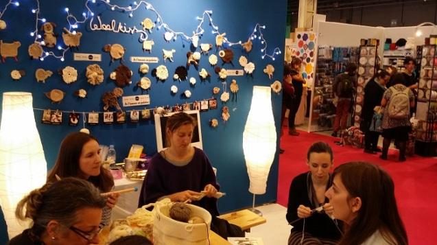 Marion du blog Bibouchka, entourée d'autres chouettes clientes restées tricoter le kit WoolKiss sur le stand